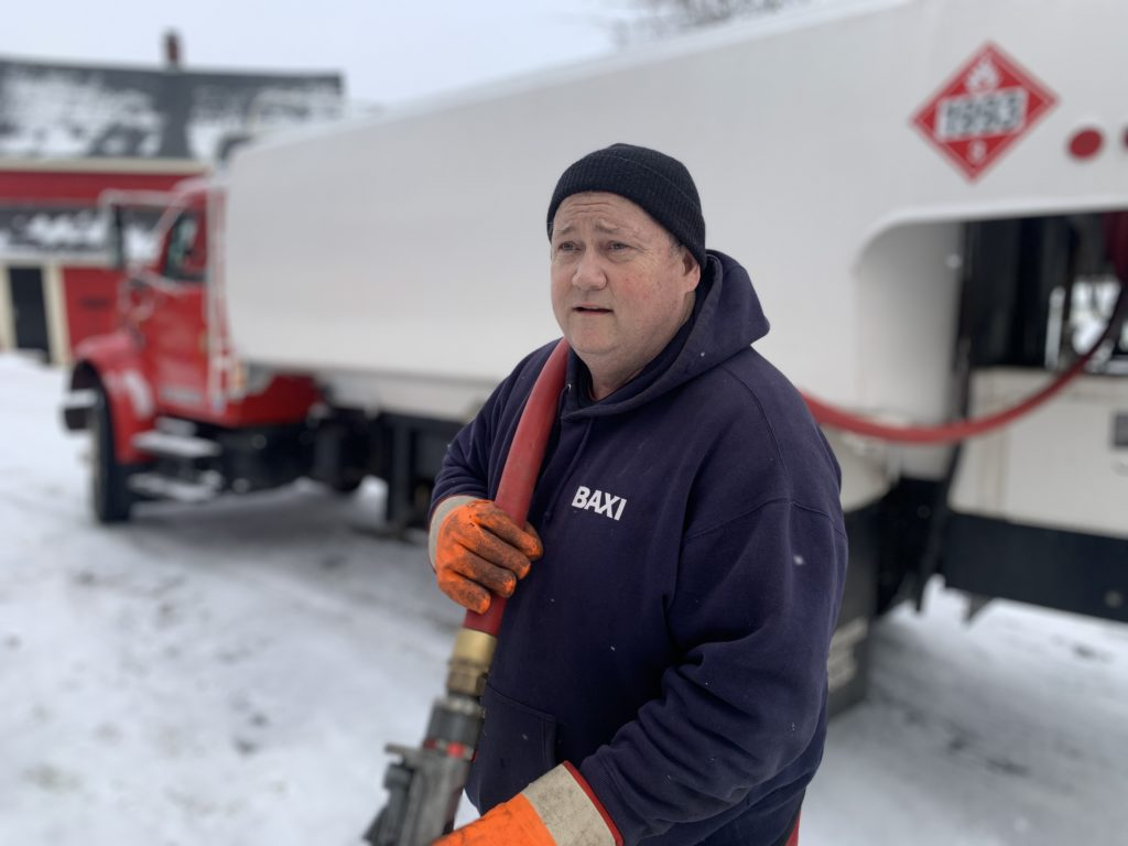 AJ pulling the oil hose to the customer's fill pipe as he prepares to fill their tank with home heating oil.